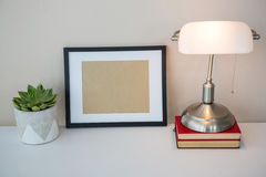 Picture frame, books, table lamp and potted plant on table Royalty Free Stock Image