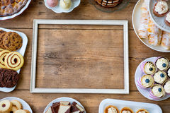 Picture frame and cake, cookies, cakepops, cupcakes. Copy space. Stock Photography