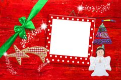 Picture frame Christmas greeting card. Funny red polka dot frame, angel, fir tree, bow and star on red wooden background Royalty Free Stock Images