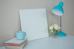 Picture frame, coffee cup with table lamp and flower vase Royalty Free Stock Photo
