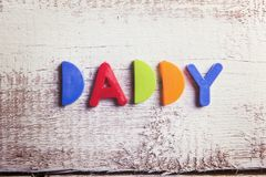 Picture frame. Colorful Daddy sign on a white wooden background Stock Photos