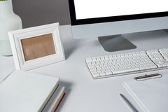 Picture frame, desktop pc and books on table Royalty Free Stock Photo