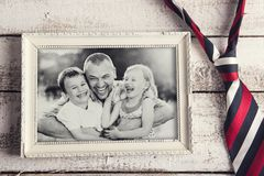 Picture frame. With family photo and colorful tie laid on wooden backround Stock Photo