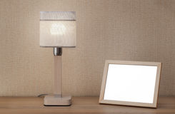 Picture frame and lamp. Blank picture frame and lamp on wooden table Stock Photography