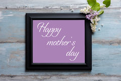 Picture frame with lilac flowers and Happy Mother`s day message on blue background Stock Images