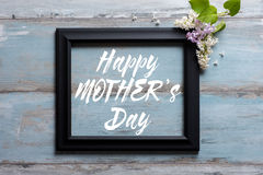 Picture frame with lilac flowers and Happy Mother`s day message on wooden background Royalty Free Stock Photos