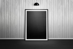 Picture frame mockup. Frame leaning on white wooden wall. Black lamp hanging Stock Photo
