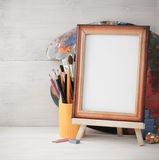 Picture frame and paints on wood Royalty Free Stock Photography