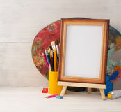 Picture frame and paints on wood Royalty Free Stock Photo