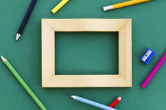 Picture frame with pencil crayons. Empty picture frame on a green background with pencil crayons and pencil sharpener Royalty Free Stock Images