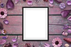 Picture frame on pink wooden desk surrounded with flower decorations Royalty Free Stock Image