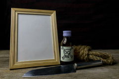 Picture frame and poison and knife. Concept Romance Suspense Stock Photos