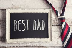 Picture frame. Rectangle picture frame with Best dad sign and colorful tie laid on wooden floor backround Royalty Free Stock Image