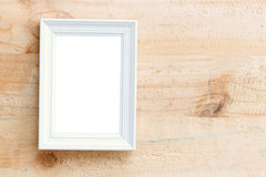 Picture frame. White picture frame with space on brown wooden wall background Royalty Free Stock Image