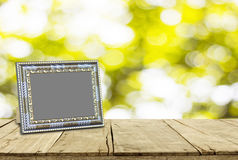 Picture frame on wooden floor and bokeh for background texture Royalty Free Stock Photos