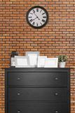 picture frames collages on black wooden cabinet and clock in empty room with red brick wall background, loft style stock photography