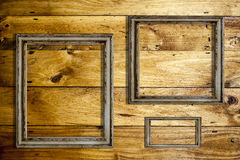 Picture frames. Three empty picture frames over a wooden background Stock Image