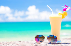 Picture of fresh banana and pineapple juice and sunglasses on tropical beach Royalty Free Stock Images