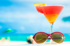 Picture of fresh red and yellow cocktail with sunglasses near tropical Stock Photos