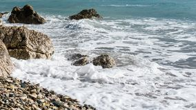 Picture of frothy sea, pebble beach, stones. In afternoon Stock Photography