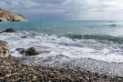 Picture of frothy sea, pebble, cloudy sky. During day Royalty Free Stock Photo