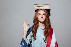 Funny redhead young lady holding book on head wearing USA flag Royalty Free Stock Image