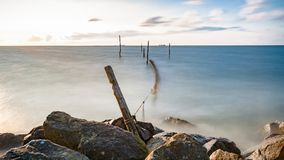 Picture of a fyke or fishing net at the IJsselmeer lake in the N. A lake at sunset with traditional fishing gear and waves that hit the coast Royalty Free Stock Photography