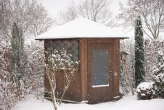 Picture of the garden and wooden garden house in the winter during a heavy snowing covered by snow. Royalty Free Stock Photo