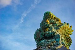 Picture of Garuda statue as Bali landmark with blue sky as a background. Balinese traditional symbol of hindu religion. Landscape picture of Garuda statue as royalty free stock image