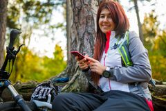 Picture of girl with cellular phone in autumn forest Royalty Free Stock Image