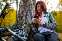 Picture of girl with cellular phone in autumn forest Royalty Free Stock Photography