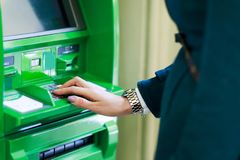 Picture of girl in coat at green cash machine. In room stock photos