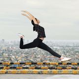 Girl does a gymnastic split on a rooftop. Picture of a girl doing a gymnastic split, png available stock image