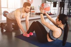 A picture of girl doing some abs exercise with the ball while her sport partner is holding her legs down on the floor. He helps her to do exercise in proper Stock Photography
