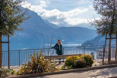 A picture of a girl on a hill on background lake Lugano and Alps mountains in Ticino canton of Switzerland stock photography