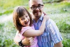 Picture of girl and man with down syndrome. Picture of girl and men with down syndrome hugging in countryside Stock Image