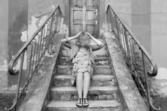 girl sitting on stairs, holding her moving head royalty free stock photos