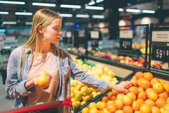A picture of a girl standing near big basket of citrus. She has chosen one orage and trying to choose some more of it. There is a piece of gates on the photo Royalty Free Stock Images