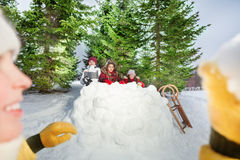Picture of girl throwing snowball at snow tower Royalty Free Stock Images