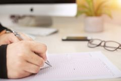 Picture of glasses, phone and man filling of omr sheet with pen royalty free stock photography