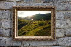 The picture in a gold frame on a background of an old brick wall Stock Photos