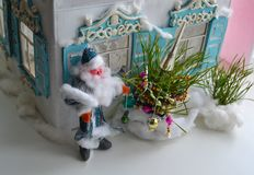 Plasticine Father Frost, New Year tree and Russian house. Picture of Grandfather Frost that standing near Russian house with Christmas tree Stock Photos