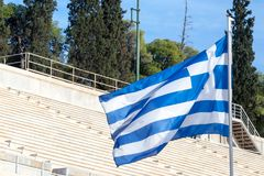 Greek flag waiving in the air in Athens, Greece. The stairs and seats of the Panathenaic stadium can be seen in the background. Picture of a Greek flag waiving Royalty Free Stock Photos