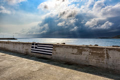 Picture of Greek flag on wall of promenade with stormy sky in Sitia town, Crete island, Greece Royalty Free Stock Photo