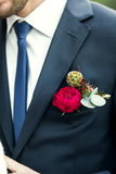 Picture of groom with blue tie and red rose boutonniere on wedding day Stock Images