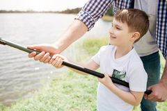 A picture of guy helping his son to hold fish-rod in a right way. He is holding it with one hand while boy is doing that. With two hands. Small men seems like royalty free stock photography
