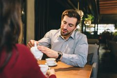 A picture of guy sitting at the table with his girlfriend and pouring some tea into the cup for them. He is listening to. Her very careful and accurate royalty free stock photography