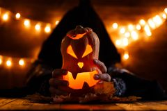 Picture of halloween pumpkin cut in shape of face with witch. On background with burning yellow lights stock photography