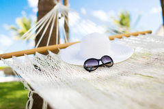 Picture of hammock with white hat and sunglasses Royalty Free Stock Photos