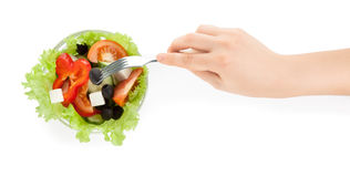 Picture of hand with fork with greek salad Stock Images